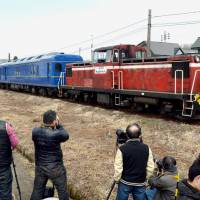 A diesel-powered express train runs in Akita Prefecture in April last year as railroad buffs standing beside the tracks take photographs. | KYODO