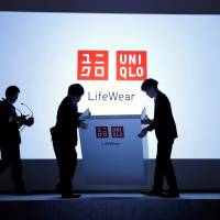 People prepare for a news conference by Fast Retailing Co. in Tokyo on March 16. | REUTERS