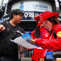 South Korean tourist information helpers guide tourists in the popular Myeongdong shopping district in Seoul on Tuesday. | AFP-JIJI
