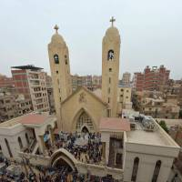 People gather outside the Mar Girgis Coptic Church in the Nile Delta City of Tanta, about 100 km north of Cairo after a bomb blast struck worshipers celebrating Palm Sunday. | AFP-JIJI