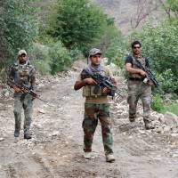 Afghan Special Forces patrol at the site of the MOAB, or 'mother of all bombs,' in the Achin district of the eastern province of Nangarhar, Afghanistan, Sunday. | REUTERS