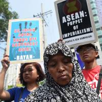 Protesters prepare to march toward the venue of the ASEAN summit in Manila on Saturday. | AFP-JIJI