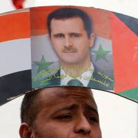 A Palestinian demonstrator holds a placard with a poster depicting Syrian President Bashar Assad during a protest against U.S. airstrikes in Syria, in the West Bank city of Nablus, on Sunday | REUTERS