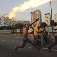 Militias blamed as two are shot dead during 'mother of all marches' in Venezuela