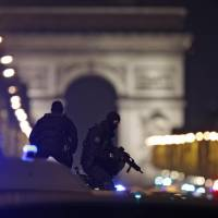 Masked police stand on top of their vehicle on the Champs Elysees Avenue after two policemen were killed and another wounded in a shooting incident in Paris Thursday. | REUTERS