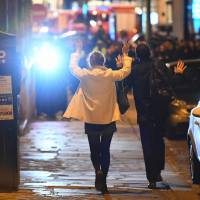 People hold their hands up as they walk toward police officers before being controlled near the site of a shooting at the Champs Elysees in Paris on Thursday.   AFP-JIJI