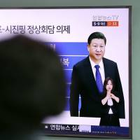 A woman watches a TV news program reporting about the first summit between U.S. President Donald Trump and Chinese President Xi Jinping, at Seoul Train Station in the South Korean capital Thursday. | AP
