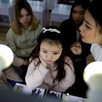 Girls get make-up training at the livestreaming talent agency Three Minute TV in Beijing in February. | REUTERS
