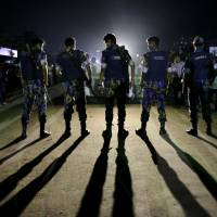 Security personnel block a road outside the Kashimpur jail during the execution of three Islamists in Dhaka Thursday. | REUTERS