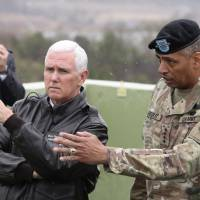 U.S. Vice President Mike Pence is briefed by Gen. Vincent Brooks, commander of the United Nations Command, U.S. Forces Korea and Combined Forces Command, from Observation Post Ouellette in the demilitarized zone (DMZ), near the border village of Panmunjom, South Korea, on Monday. | AP
