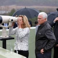 U.S. Vice President Mike Pence watches Monday as his daughter peers into North Korea from the Demilitarized Zone separating the two Koreas. | REUTERS