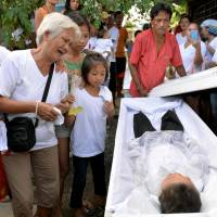 The grandmother of 5-year-old Francisco Manosca, son of Domingo Manosca, who according to relatives was a drug user, mourns during his funeral in the metropolitan Manila city of Pasay on Dec. 21. According to relatives and neighbors, unidentified gunmen killed both the father and child at their home. | REUTERS