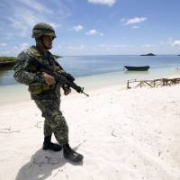 A Filipino soldier patrols the shore of Thitu Island, which is known in the Philippines as Pagasa Island, in the Spratly chain of the disputed South China Sea in May 2015. | REUTERS