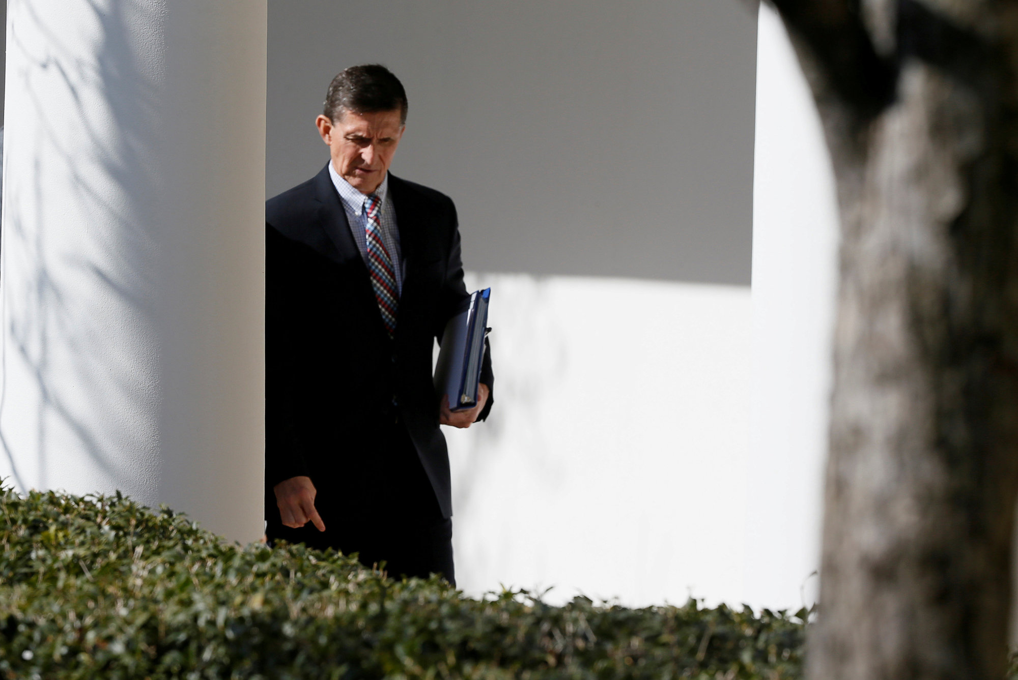 White House National Security Advisor Michael Flynn walks down the White House colonnade on the way to the joint news conference of President Donald Trump and Prime Minister Shinzo Abe on Feb. 10. | REUTERS