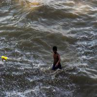 An Indian boy walks along a flooded bank of the Ganges River in Allahabad on July 10, 2016. | AFP-JIJI