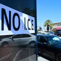 Motorists pass a 'No I.C.E' protest statement posted on bus stop exterior in Bell Gardens, California, on Tuesday. Southern California's heavily Latino immigrant communities have been gripped by fear of U.S. Immigration and Customs Enforcement raids and deportations as Democrats push for a ban on ICE from courthouses. | AFP-JIJI