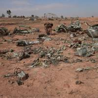 A Syrian Democratic Forces (SDF) fighter inspects destroyed airplane parts inside Tabqa military airport after taking control of it from Islamic State fighters, west of Raqqa city, Syria, Sunday. | REUTERS