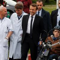 French presidential election candidate for the En Marche ! movement Emmanuel Macron (center) talks with doctors during his visit at the Raymond Poincare hospital in Garches outside Paris Tuesday. | PHILIPPE WOJAZER / POOL / VIA AFP-JIJI