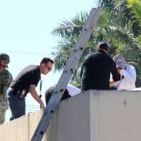 A soldier stands guard as forensic technicians work at a crime scene where the body of a man, who witnesses said was tossed from a plane, landed on a hospital roof in Culiacan, in Mexico's northern Sinaloa state Wednesday. | REUTERS