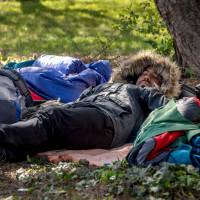 Kurd migrants rest in front of the gymnasium where some of them took shelter after a huge blaze destroyed the Grande-Synthe campTuesday in Grande-Synthe, France. | AFP-JIJI