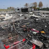 Burned remains of a migrant camp are seen in the Dunkirk suburb of Grande-Synthe, northern France, Tuesday. | AP