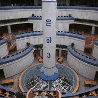 Study tables are dwarfed against the base of a model of the Unha 3, a space launch vehicle, displayed at the Sci-Tech Complex Monday in Pyongyang. Tensions have spiked in recent weeks over North Korea's advancing nuclear technology and missile arsenal. But in Pyongyang, where war would mean untold horrors, where neighborhoods could be reduced to rubble and tens of thousands of civilians could be killed, few people seem to care much at all. | AP