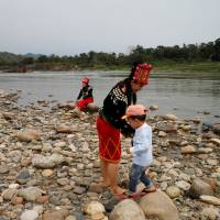 Ethnic Kachin people visit Myitsone, the confluence of the Mali and Nmai rivers, outside Myitkyina, Myanmar, on March 30. | REUTERS