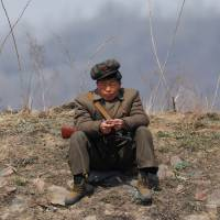 A North Korean soldier sits on a bank of the Yalu River just north of Sinuiju on Sunday. | REUTERS