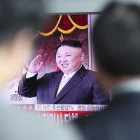 People passing through a train station in Seoul on Saturday morning watch a live television program showing North Korean leader Kim Jong Un saluting as he attends a huge military parade in Pyongyang.   AP