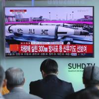South Koreans watch a live broadcast of a Pyongyang military parade on Saturday at Seoul Station. The missile shown here is a submarine-launched Pukguksong-1 ballistic missile.   AP