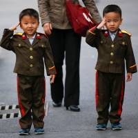 Boys wearing military uniforms salute as they are photographed at a zoo in Pyongyang on Sunday. | REUTERS