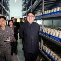 This undated picture released Saturday shows North Korean leader Kim Jong Un visiting the Pyongyang Mushroom Farm in the country's capital. | AFP-JIJI