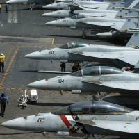 A row of F-18 fighter jets sit on the deck of the USS Carl Vinson aircraft carrier during a patrol in the disputed South China Sea on March 3. | AP