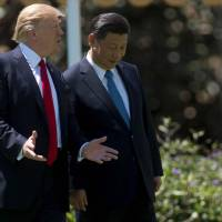 U.S. President Donald Trump and Chinese leader Xi Jinping speak during a stroll on the grounds of Trump's Mar-a-Lago estate in Palm Beach, Florida, on Friday. | AFP-JIJI