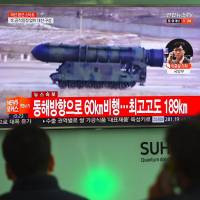 People watch a television displaying file news footage at a railway station in Seoul on Wednesday of a North Korean missile launch after the nuclear-armed North fired a ballistic missile into the Sea of Japan earlier in the day. | AFP-JIJI