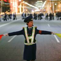 A policewoman controls traffic as people gather near the main Kim Il Sung square in central Pyongyang Tuesday. | REUTERS