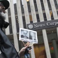 Activist Judah Friedlander holds his 'Activist Barbie' with a photo of Bill O'Reilly (right) next to politician Bull Connor, who strongly opposed activities of the American Civil Rights Movement in the 1960s, in front of the News Corp. headquarters in Midtown Manhattan Wednesday. O'Reilly has lost his job at Fox News Channel after allegations that he sexually harassed women. | AP
