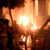Hundreds of demonstrators protesting against the approval of a constitutional amendment for presidential re-election broke into Paraguay's Congress building in Asuncion on Friday, battering down entrances and fences and shattering windows, and started to set fires inside. | AFP-JIJI