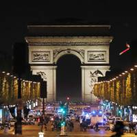 Police block access to the Champs Elysees in Paris on Thursday following a terrorist attack that left a policeman dead and two wounded. | AFP-JIJI