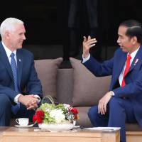 U.S. Vice President Mike Pence (left) chats with Indonesia President Joko Widodo at the presidential palace in Jakarta Thursday. | REUTERS