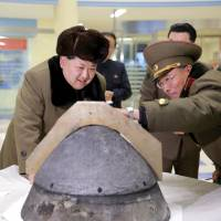 North Korean leader Kim Jong Un looks at a rocket warhead tip after a simulated test of atmospheric re-entry of a ballistic missile at an unidentified location in this undated photo released in March 2016. | REUTERS