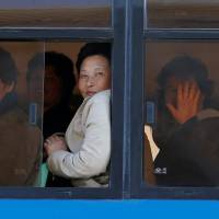Women react from a bus in central Pyongyang, North Korea on Wednesday.   REUTERS