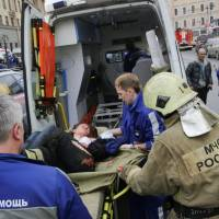 An injured person is helped by emergency services outside Sennaya Ploshchad station, following explosions in two train carriages at metro stations in St. Petersburg, Russia on Monday. | REUTERS