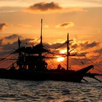 A Philippine boat fishes during sunset at the disputed Scarborough Shoal in the South China Sea on Wednesday. | REUTERS