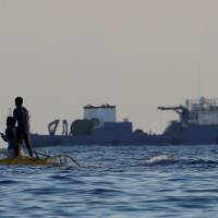 Filipino fishermen fish near a large Chinese vessel at the disputed Scarborough Shoal in the South China Sea on Wednesday | REUTERS