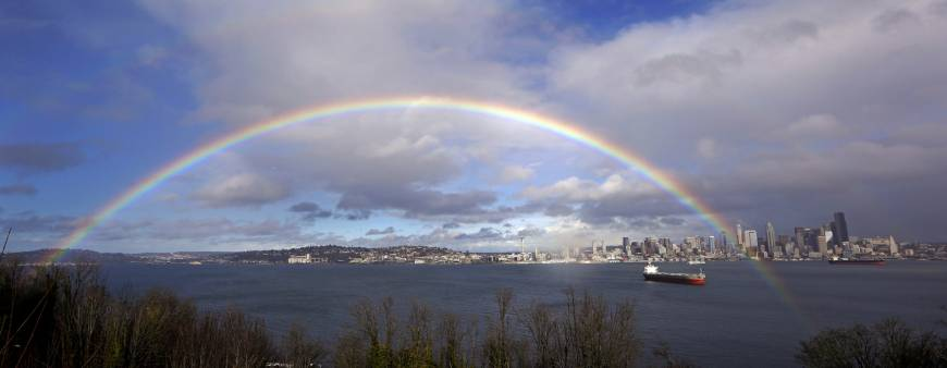 A rainbow arc fills the sky and spreads across Elliott Bay and downtown Seattle between rain showers in February. The National Weather Service says the city has measured 44.67 inches of rain in the city between October 2016 and so far in April. That makes it the wettest such period since records began in 1895. | AP
