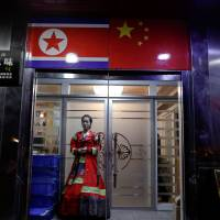 A woman wearing traditional Korean costume waits at the door of a North Korean restaurant in Dandong city, in north China's Liaoning province, on March 30. | REUTERS