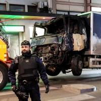 A truck that plowed into a crowd Friday on a central Stockholm shopping street and crashed into a department store is towed away early Saturday. | REUTERS