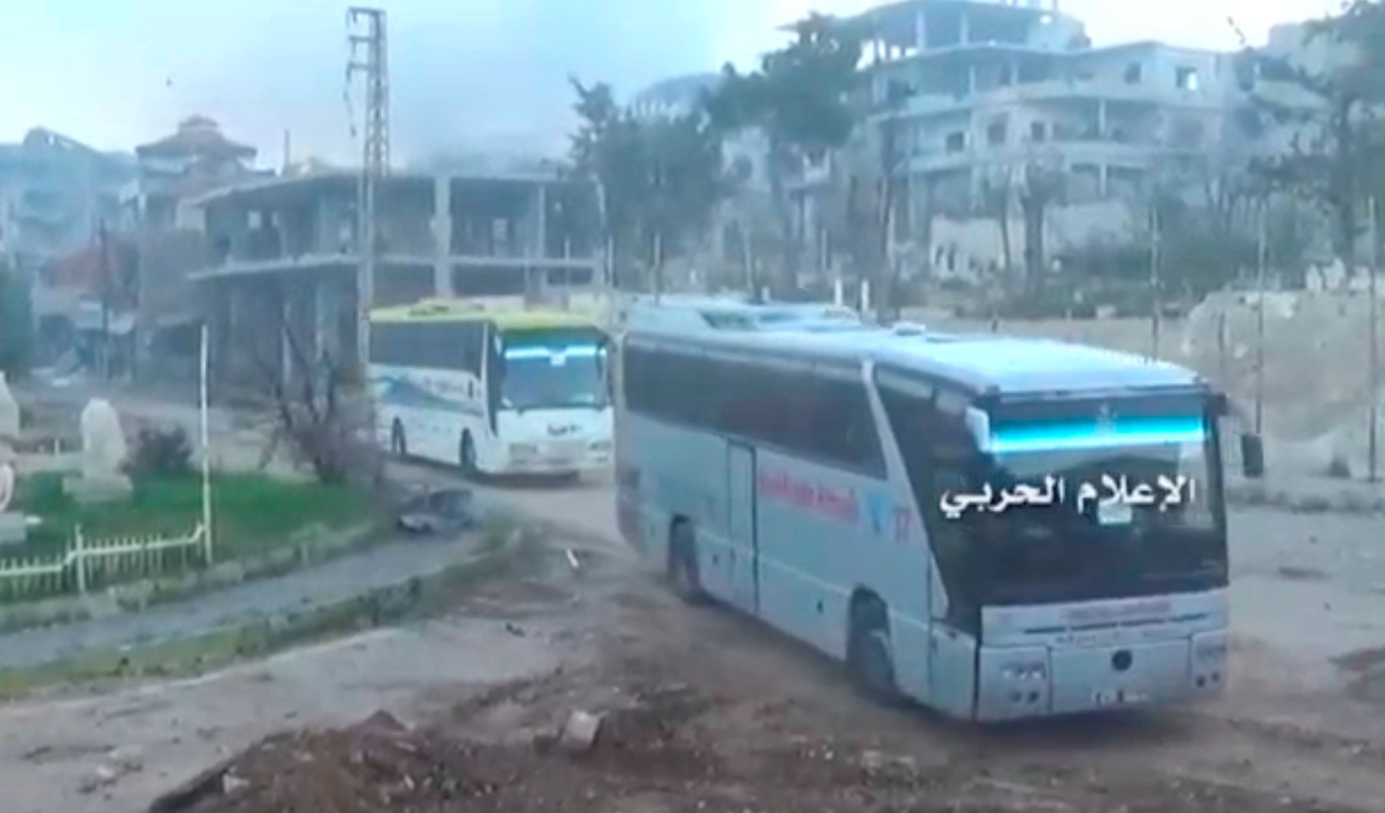 A still image taken from a video uploaded by the Syrian Army on Wednesday shows buses carrying rebel fighters and their families leaving the the town of Zabadani, near Damascus. | SYRIAN ARMY / HANDOUT / VIA REUTERS TV