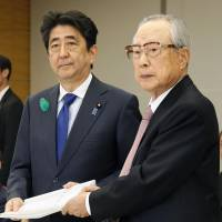 Takashi Imai, chairman of the government's expert panel on Emperor Akihito's abdication, submits its final report to Prime Minister Shinzo Abe on Friday at the Prime Minister's Office in Tokyo. | KYODO